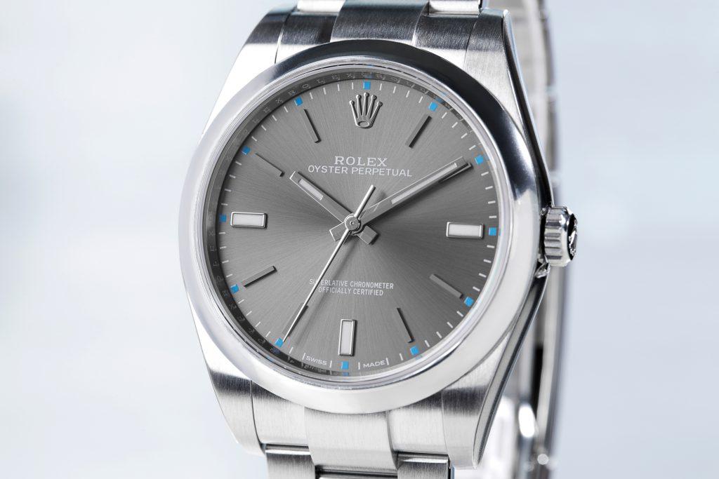 Nahaufnahme einer Rolex Oyster Perpetual 114300 mit grauem Zifferblatt auf hellblauem Hintergrund
