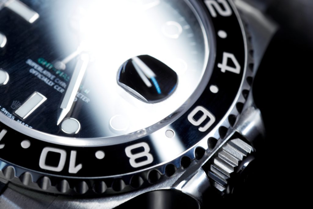 Dial of a Rolex GMT-Master II 116710LN watch with date window and cyclops lens