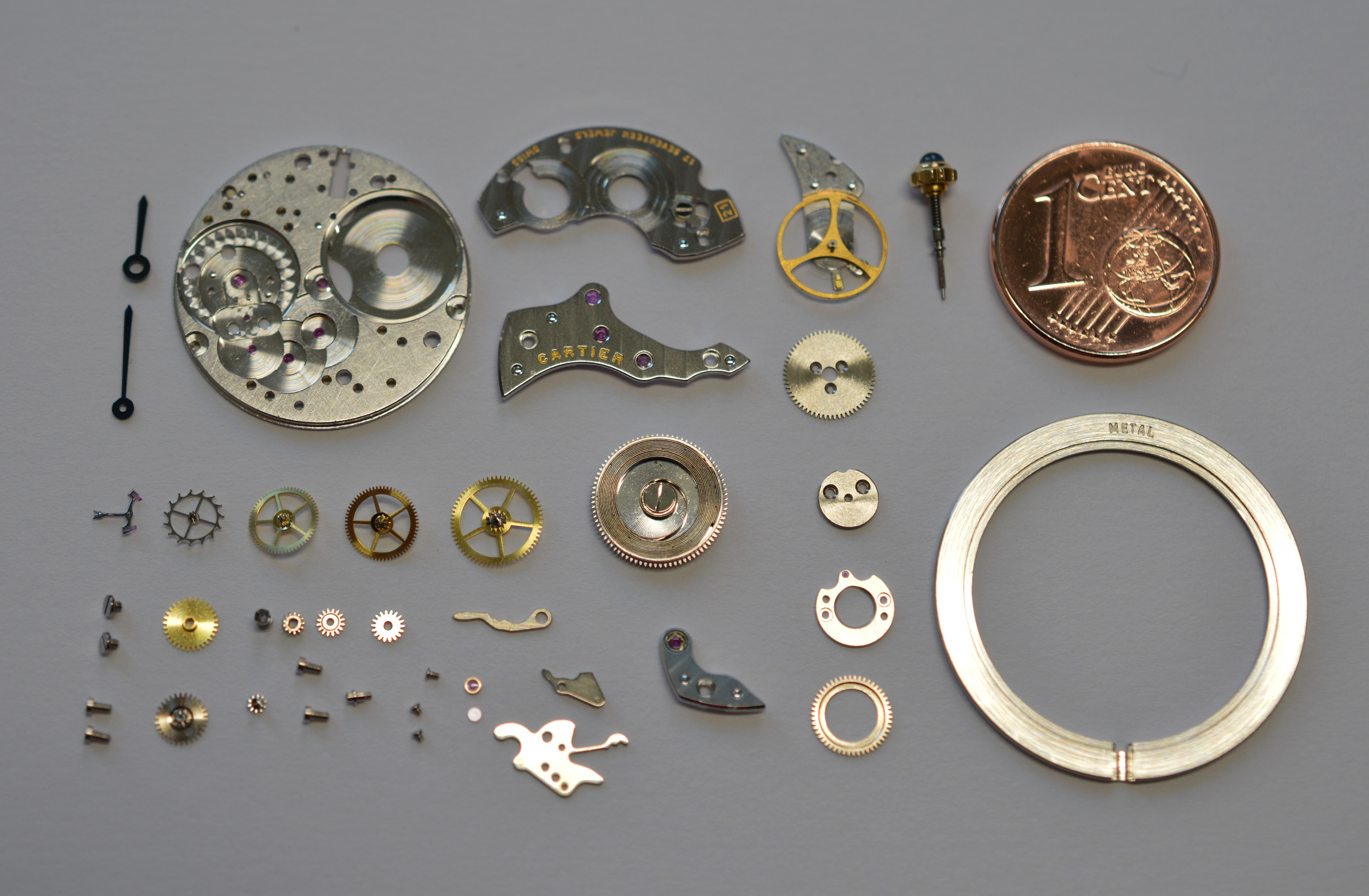 Individual components of a Cartier three-hand watch movement on a grey surface