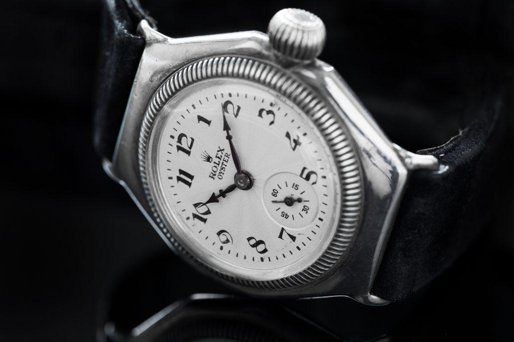 Die erste wasserdichte Uhr: Rolex Oyster mit weißem Zifferblatt und schwarzem Lederarmband auf schwarzem Hintergrund
