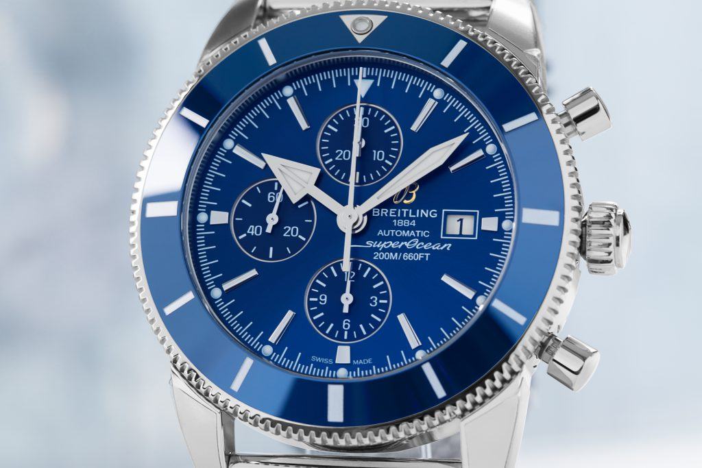 Close-up of a Breitling Superocean Heritage Chronograph with blue dial and bezel on grey background