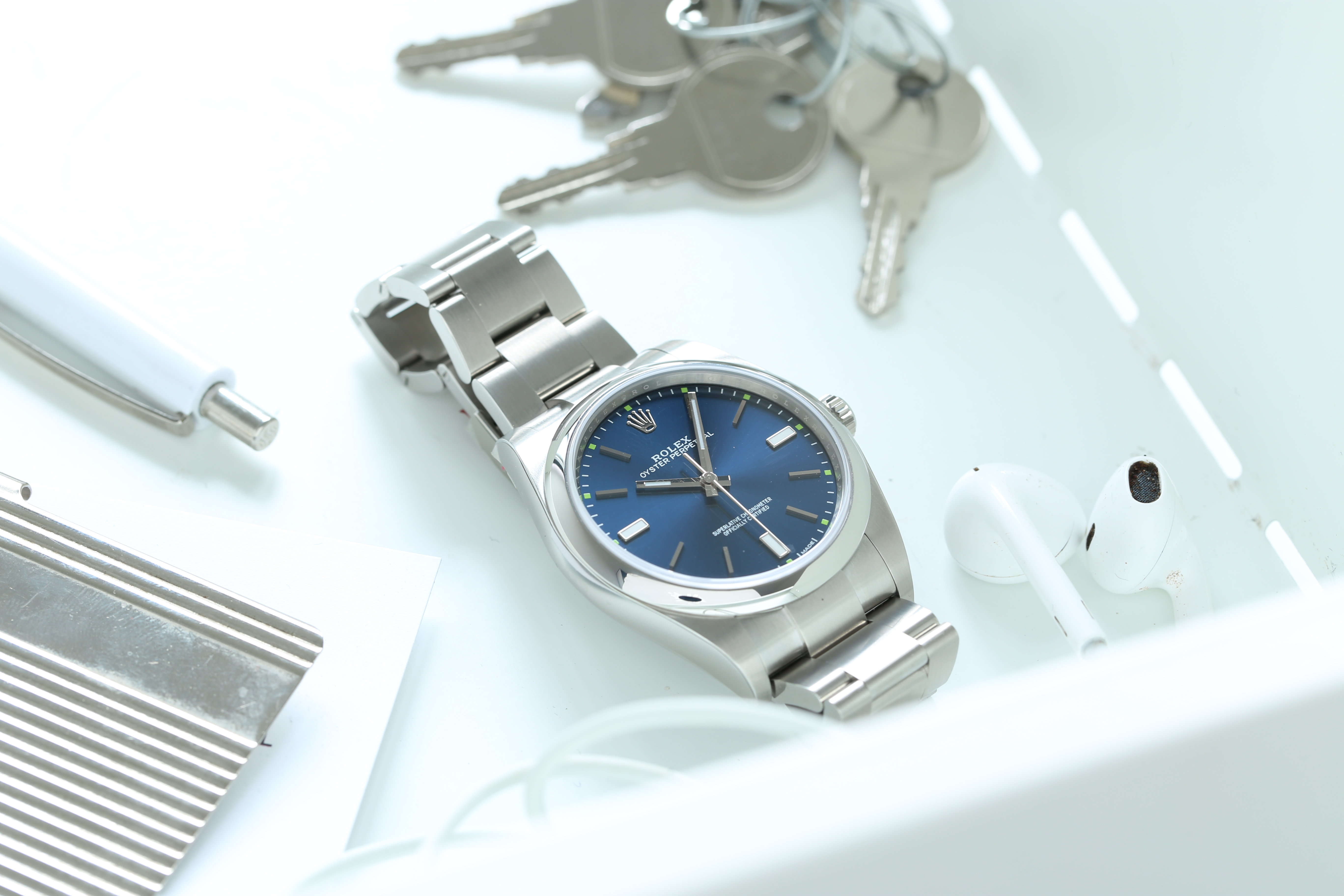 Rolex Oyster Perpetual watch with blue dial on a desk next to earpods, a pen and keys