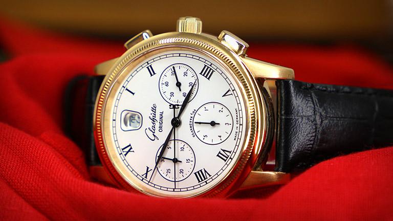 Glashütte Original-klocka med guldboett och svart armband i läder på rött tyg