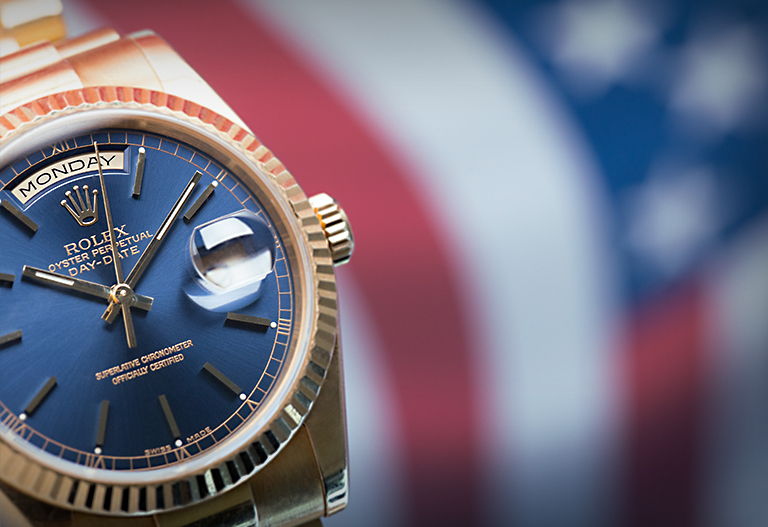 Rolex Day-Date 118238 presidential watch in yellow gold with blue dial in front of American flag