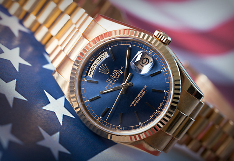 Rolex Day-Date 118238 presidential yellow gold watch with blue dial lying on the American flag