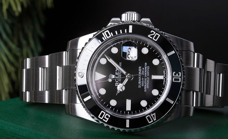 Rolex Submariner 116610LN steel watch with black bezel and black dial on a green Rolex watch box