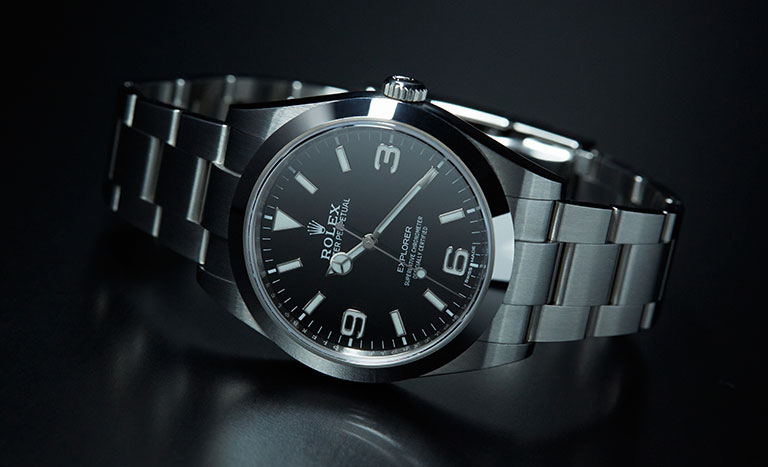 A black Rolex Explorer 214270 lying with dark background