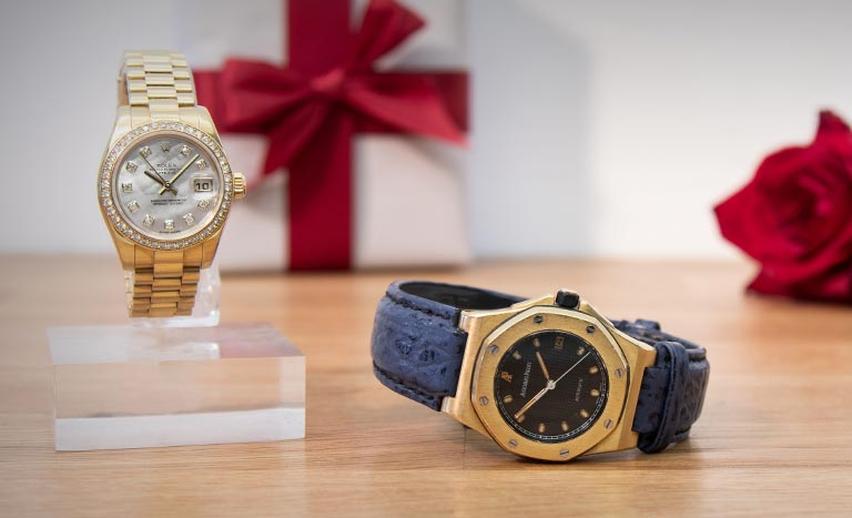 Rolex Lady-Datejust 179138 standing and Audemars Piguet Royal Oak Offshore BA77151.O.0009 lying with a present and rose in background