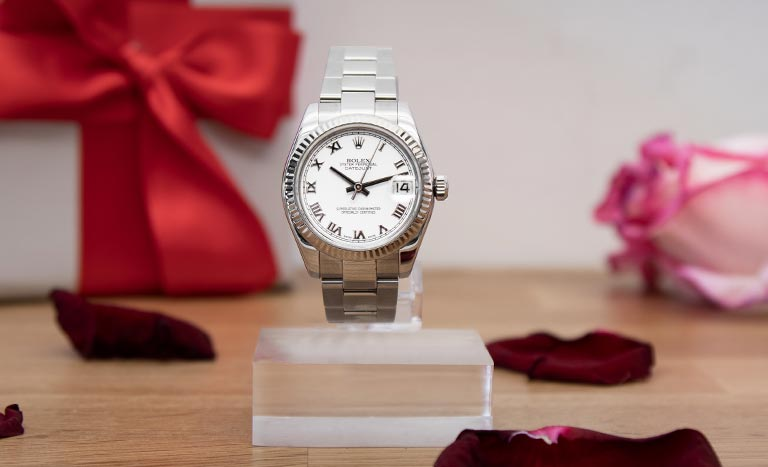 Une montre Rolex Datejust 116234 entourée de roses avec un cadeau et des pétales de rose en arrière-plan
