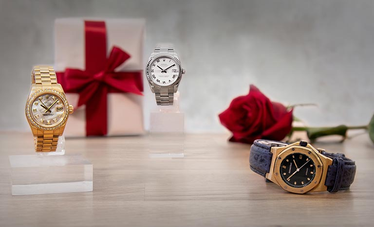 Rolex Lady-Datejust 179138, Rolex Datejust 116234 and Audemars Piguet Royal Oak Offshore BA77151.O.0009 with a gift and rose in the background