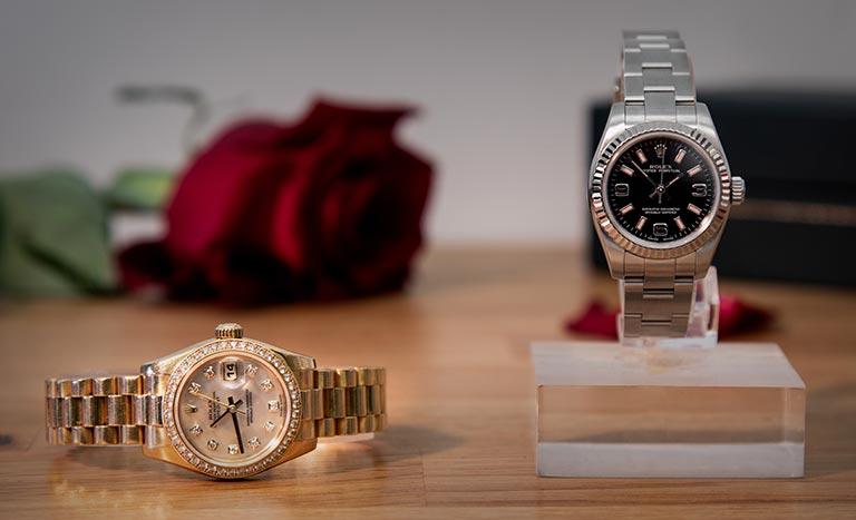 Une montre Rolex Lady Datejust 179138 couchée et une montre Rolex Lady Oyster Perpetual 176234 debout avec une rose en arrière-plan