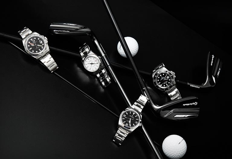 Four different Rolex watches with golf clubs and balls on a black background
