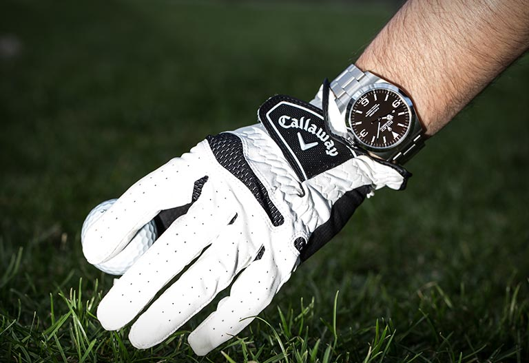 Rolex Explorer 114270 watch on a golfer's wrist and on a golf course