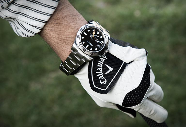 A Rolex Explorer II 216570 watch on a golfer's wrist and on a golf course