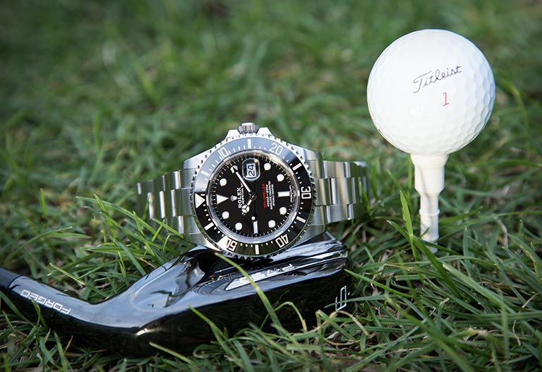 Rolex Sea-Dweller 126600 on the grass near a golf ball