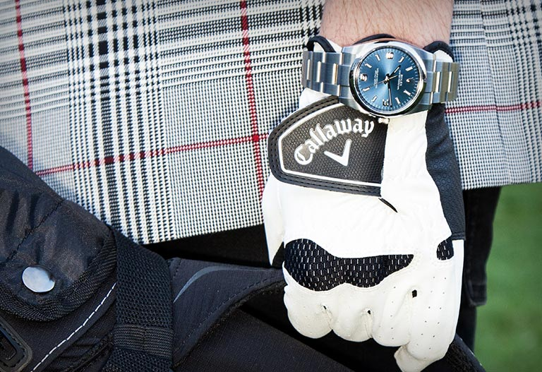 A Rolex Oyster Perpetual 114200 watch on a golfer's wrist and on a golf course