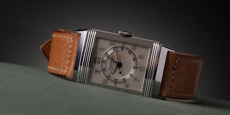 An Jaeger LeCoultre watch with a leather bracelet on a green background