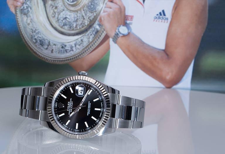 Rolex Datejust 126334 Uhr mit schwarzem Zifferblatt auf weißem Tisch, im Hintergrund hält Angelique Kerber einen Turnierpreis