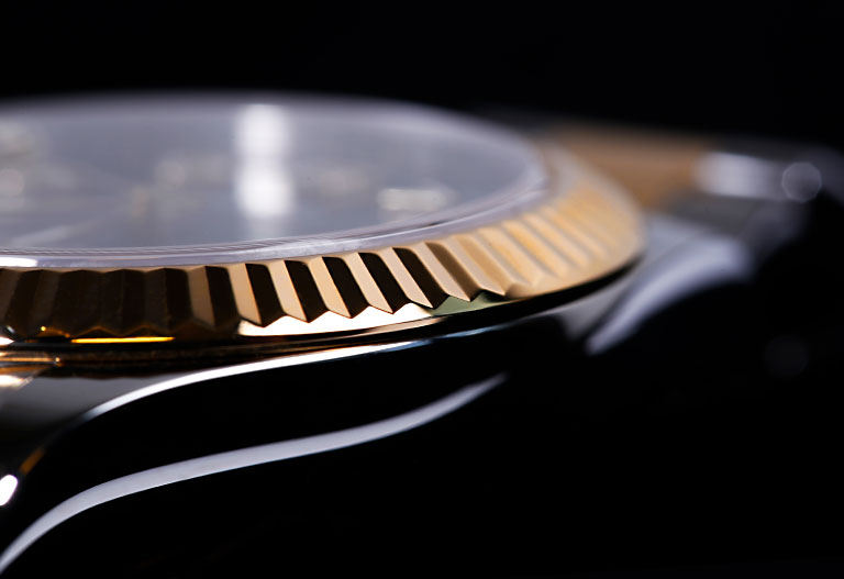 Materiales de Rolex - Detalle de un bisel de oro amarillo con caja y brazalete de Oystersteel