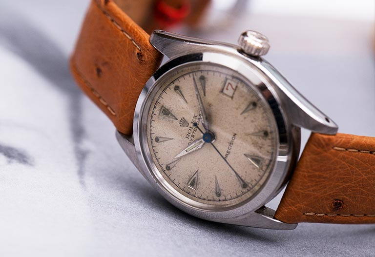 Vintage Rolex Oyster Precision watch with brown leather strap lying on white paper