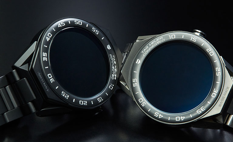 Dos relojes TAG Heuer Connected Modular 45 uno al lado del otro en una superficie reflectante negra