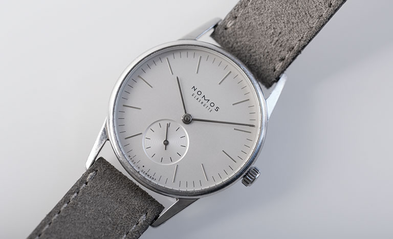 Nomos Glasshütte Orion 324 watch on light grey background