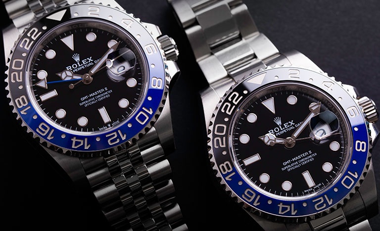 Rolex Batman 126710BLNR with Jubilee bracelet next to a Batman 116710BLNR with Oyster bracelet on grey background