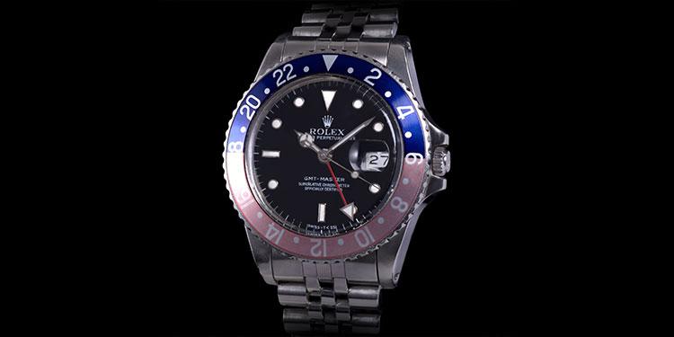 Rolex GMT-Master 16750 con bisel descolorido y brazalete Jubilee sobre fondo negro