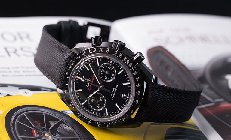 An Omega Speedmaster watch with black fabric strap lying on a magazine