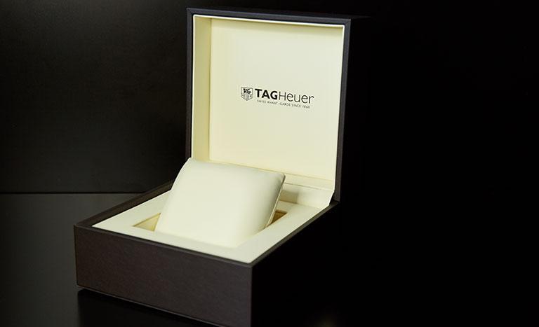 Eine geöffnete, braun-schwarze TAG Heuer Uhrenbox mit hellem Innenpolster auf schwarzem Hintergrund