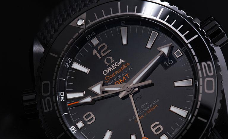 Schwarzes Zifferblatt einer Omega Seamaster Planet Ocean 600 M 215.92.46.22.01.001 Taucheruhr mit orangen Farbakzenten