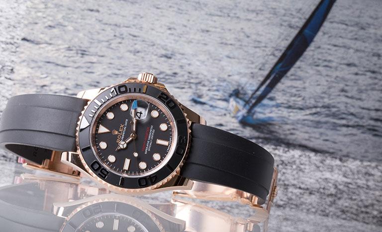Eine Rolex Yachtmaster Uhr mit einem Boot im Hintergrund.