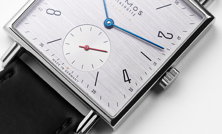 White dial of a Nomos Glashütte Tetra 408 watch with black leather strap