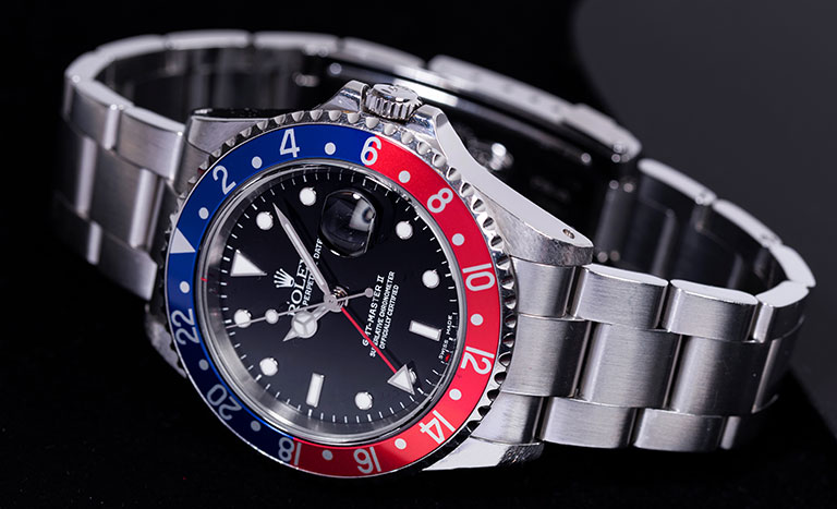 A Rolex with a Pepsi bezel on a black background.