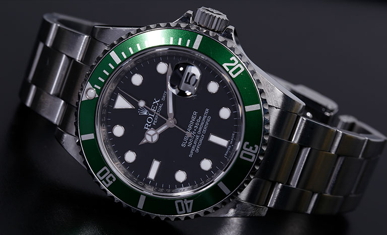 A Rolex placed on a metallic grey background.