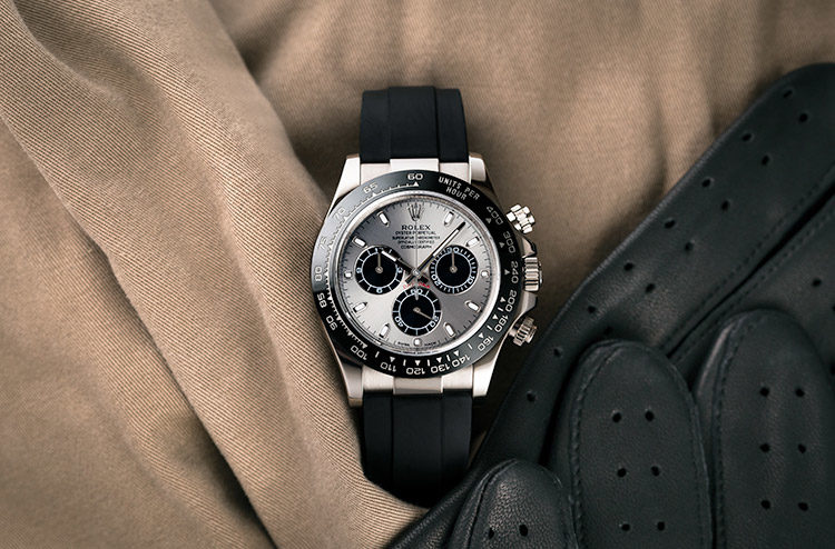 Rolex Daytona 116519LN with black rubber strap on beige fabric next to black leather gloves