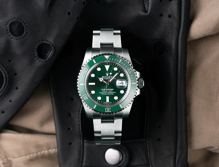 Rolex Submariner 116610LV watch with green dial and green bezel on black leather glove