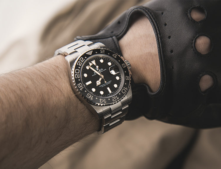 Rolex GMT-Master II 116710LN watch with black bezel on the wrist of a man wearing a black leather glove