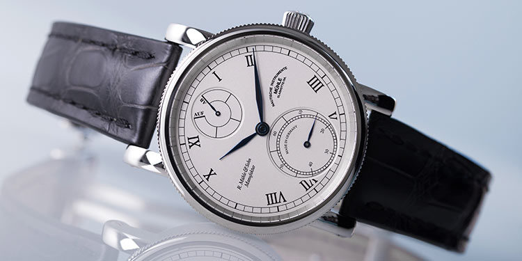 Mühle Glashütte watch with white dial and black leather strap lying on reflective surface