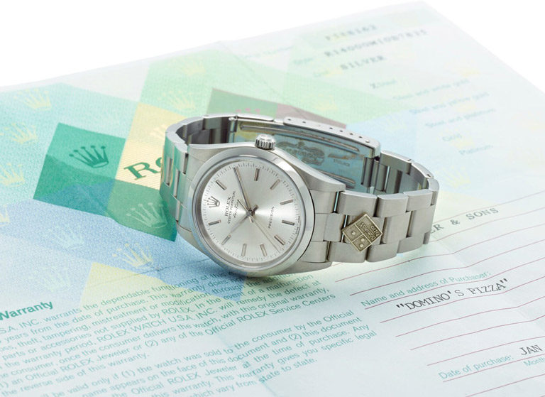 Rolex Air-King watch with Domino's logo application on bracelet lying on Rolex warranty papers