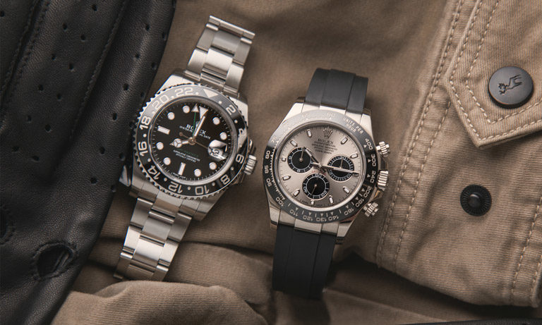 Rolex GMT-Master II 116710L and Daytona 116519LN lying next to black leather gloves on beige jacket