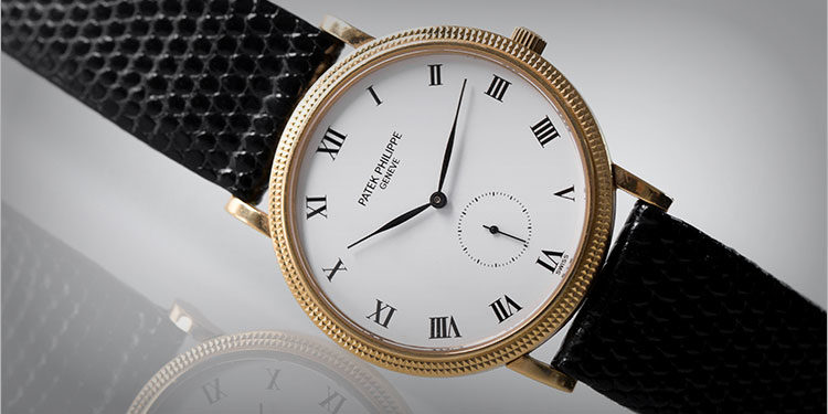 Patek Phillipe Calatrava 3919J with black leather strap lying on white surface