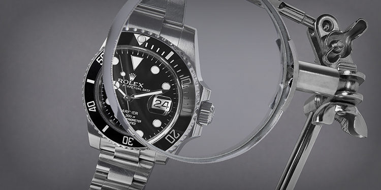 Pre-owned Rolex Submariner Date with a black dial under a magnifying glass