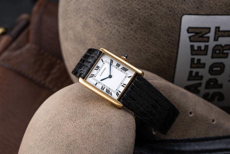 Montre Cartier Tank 1700 avec boîtier en or jaune et bracelet en cuir noir posée sur un gant de boxe