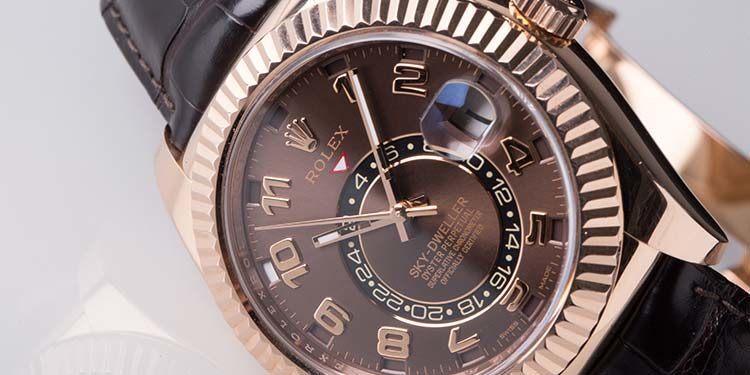 Close up of a men's watch Rolex Sky-Dweller 326135 in rose gold with leather strap and brown dial lying on a white table