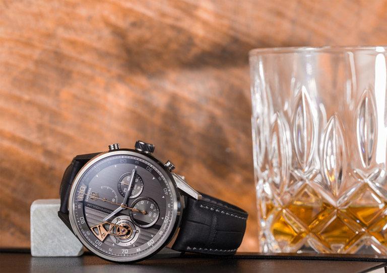TAG Heuer Carrera Mikropendulum CAR2B83.FC6339 Uhr mit Titangehäuse und grauem Zifferblatt neben Whiskeyglas