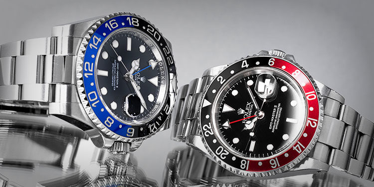 Rolex Batman 116710BLNR lying next to a Rolex Coke 16710 on a reflecting surface